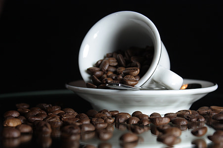 selective focus photo of white ceramic teacup on saucer with coffee beans