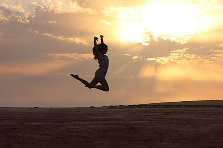 woman jumping during sunset