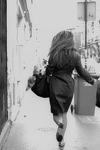 greyscale photography of woman walking on sidewalk