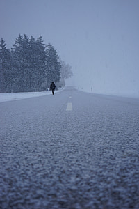 person walking on concrete road during winter