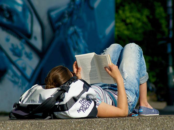 man lying on pavement reading books