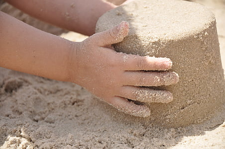 child holding pile of sand