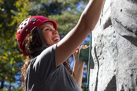 woman in gray shirt climbing on gray wall