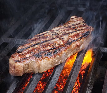 grilled beef on top of black steel charcoal grill