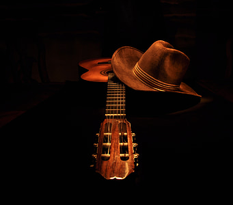 brown classical guitar and cowboy hat