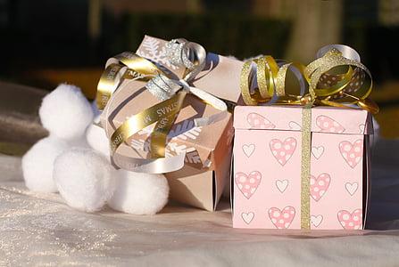 pink gift box beside white cotton balls