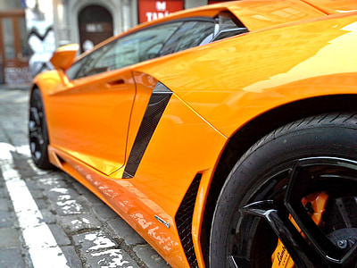 orange Lamborghini parked during daytime