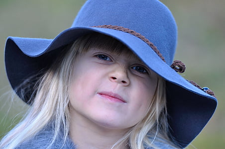 girl wearing blue hat while smiling
