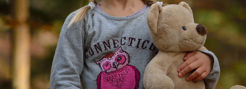 selective focus photography of girl holding bear plush toyt