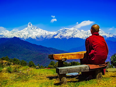 man wearing red robe sitting on black bench looking at snow covered mountain