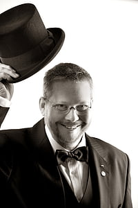 grayscale photo of man wearing notched lapel suit jacket and holding fedora hat