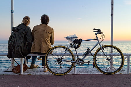 man and woman sitting on bench near bicycle