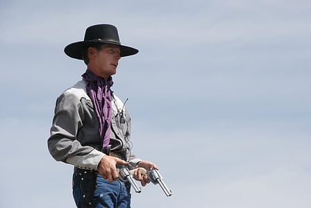 photo of man holding two gray revolvers
