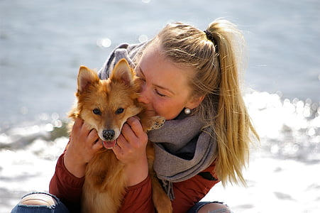 woman hugging Finnish spitz while sitting