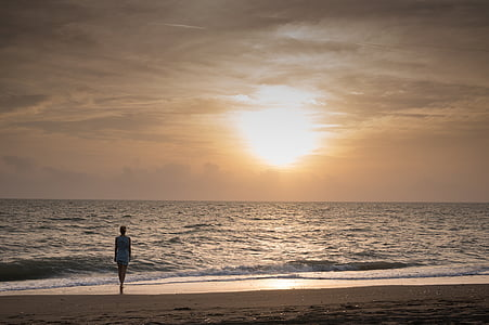 woman walking on shoreline during golden hour