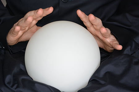 person holding round frosted glass ball