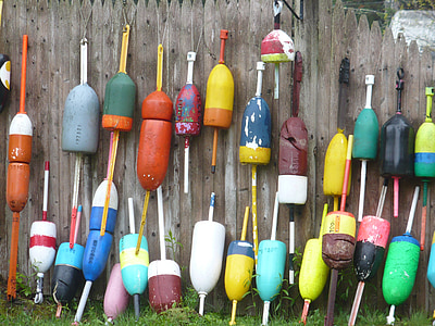 assorted-color ornaments leaning on brown wooden fence at daytime
