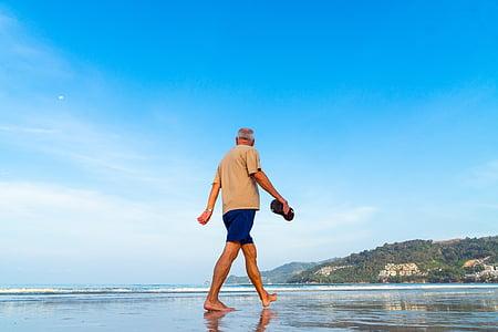 man wearing brown t-shirt and blue shorts walking on seashore during daytime