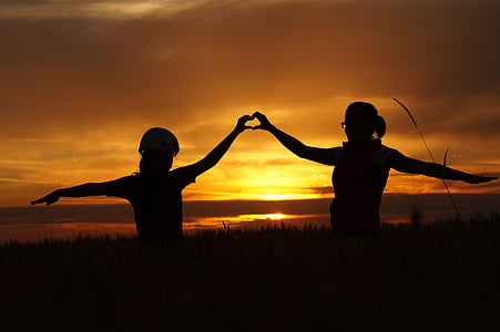 silhouette of two person during sunset