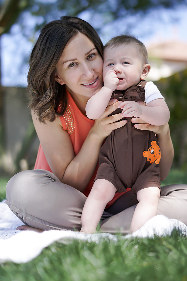 woman sitting ground holding her child during daytime