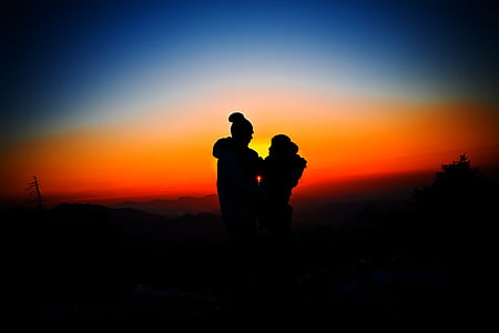 silhouette of man and woman overlooking sunset