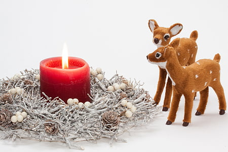 red pillar candle and two brown deer figurine