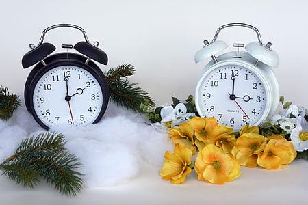 two white and black analog alarm clocks