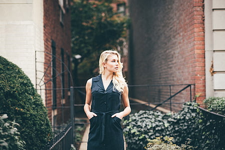 woman in black sleeveless dress standing near building in daytime