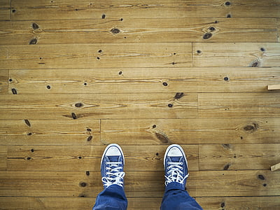high angle photo of person wearing pair of blue sneakers