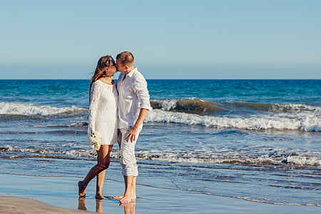 woman and man standing on shoreline kissing