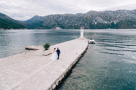 bride and groom walking on dock during daytime
