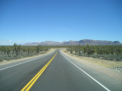 gray concrete road leading to canyons between green grass areas