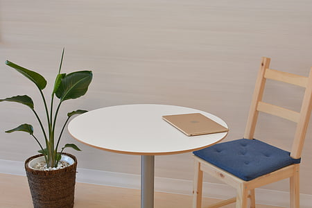 round brown wooden table beside plant