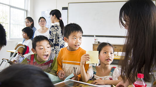 children looking at black-haired woman