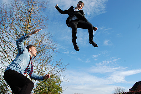 low-angle view of man and kid jumping