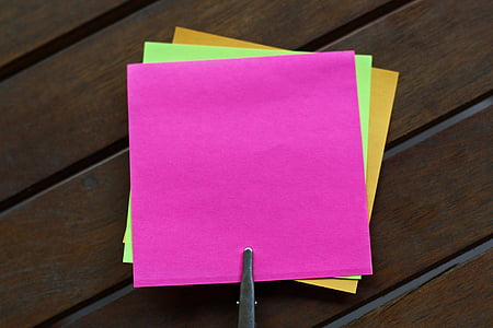 three sticky notes on brown panel