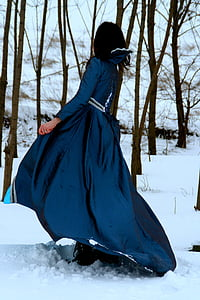 woman in blue dress walking on snow