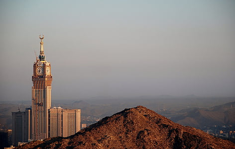 brown and gold tower clock surrounded with mountains