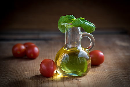 glass jug filled with oil with tomatoes on the table