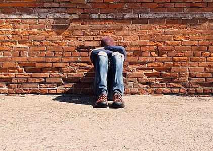 man laying on brick wall