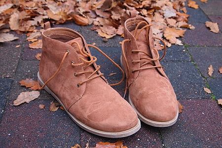 pair of brown suede high-top sneakers on gray concrete pavement