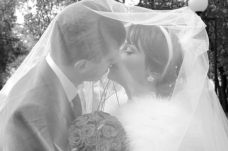 bride and groom kissing with veil