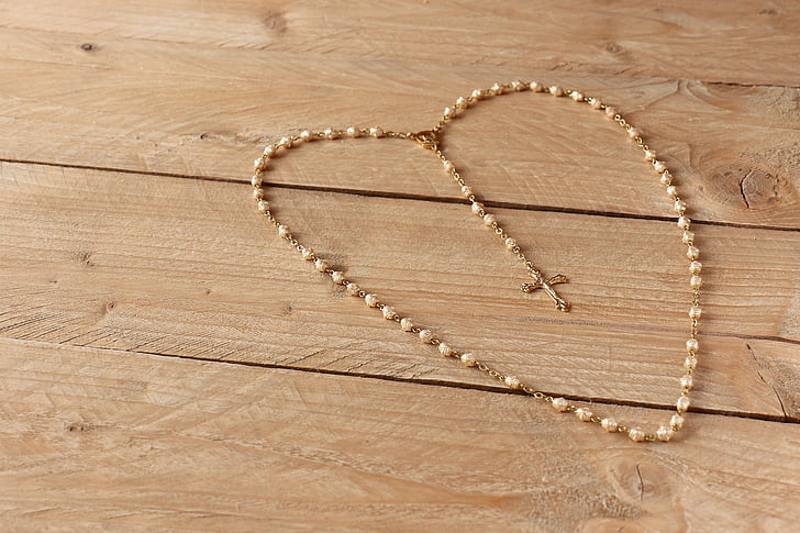 beige rosary on beige wooden frame