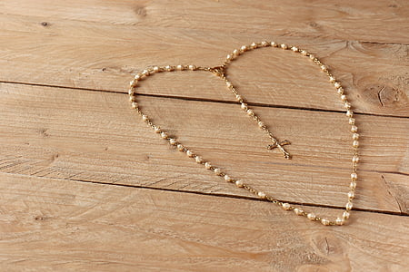 beige rosary on beige wooden frame