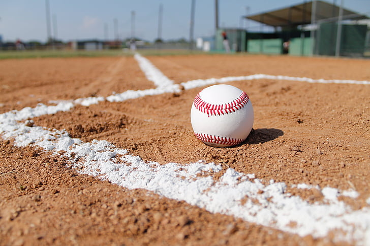 white and red baseball on brown sand