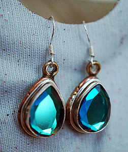 pair of gold-and-silver-colored pendant hook earrings with green gemstones