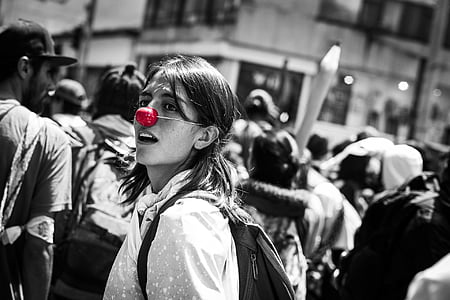 selective photography of woman wearing red nose cover