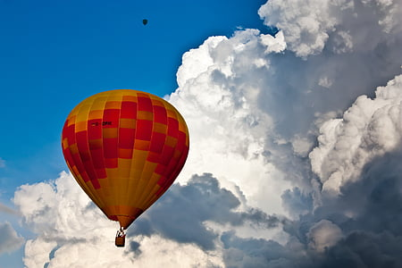 yellow and red hot air balloon near white sky during daytime