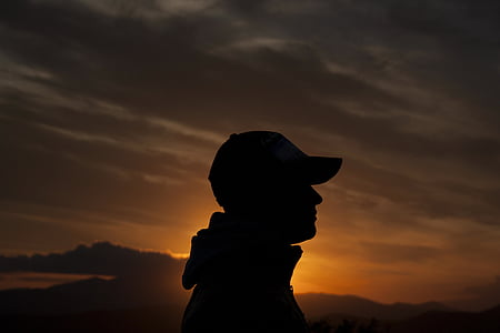 silhouette photo of person wearing cap