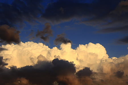 low-angle photography of beige and black clouds